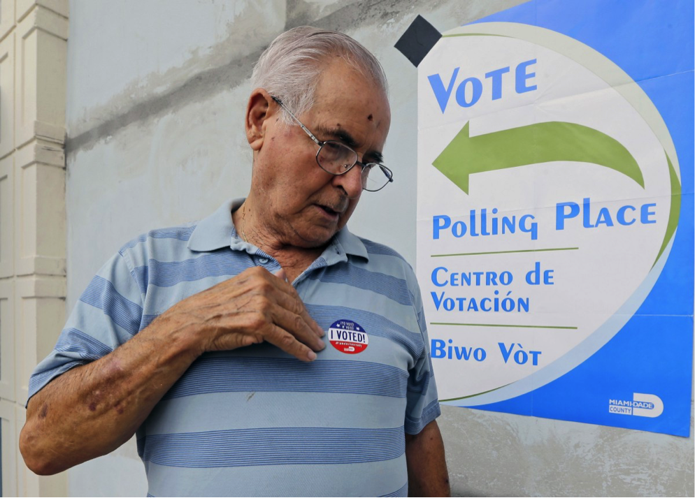 Orlando Fernandez places a sticker on his shirt after casting his primary vote, Tuesday, Aug. 30, 2016, in Hialeah, Florida. Voters approved a pro-solar measure by 70 percent. CREDIT: AP PHOTO/ALAN DIAZ