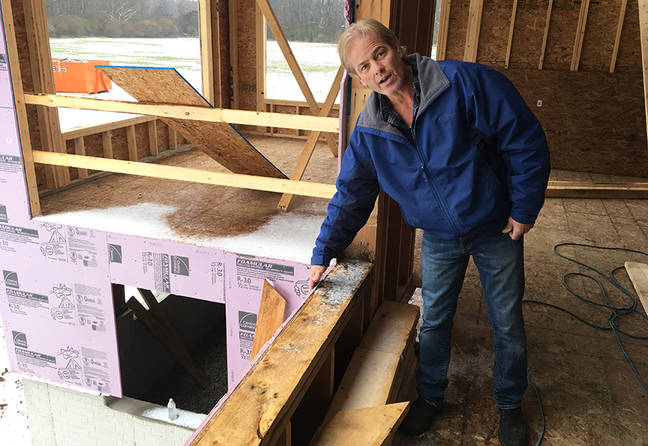 Bill Decker's son, Dale, shows some of the construction methods used to insulate and seal a highly energy-efficient home against air leaks and energy waste. Credit: Dan Gearino